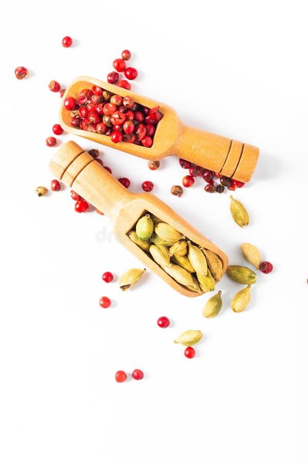Cardamome organique d'épices exotiques et cosses roses de grain de poivre dans le scoop en bambou sur le fond blanc image stock