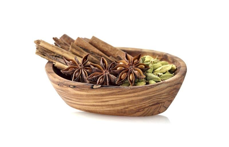 Cardamon, циннамон, анисовка в деревянном шаре на белой предпосылке Изолированные специи стоковое фото