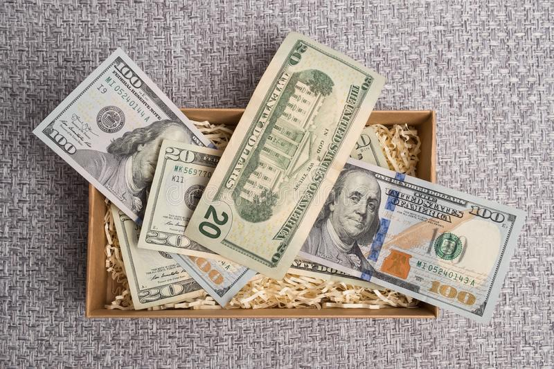 Cardboard box with american money. Banknotes in a small gift cardboard box. Dollar studio image. Notes in a carton box. Cardboard box with american money royalty free stock photo
