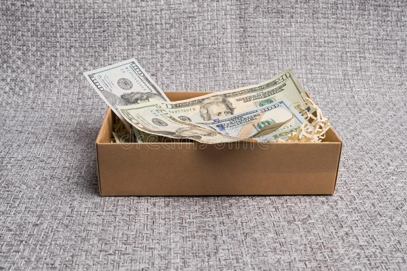 Cardboard box with american money. Banknotes in a small gift cardboard box. Dollar studio image. Notes in a carton box. Cardboard box with american money stock photos