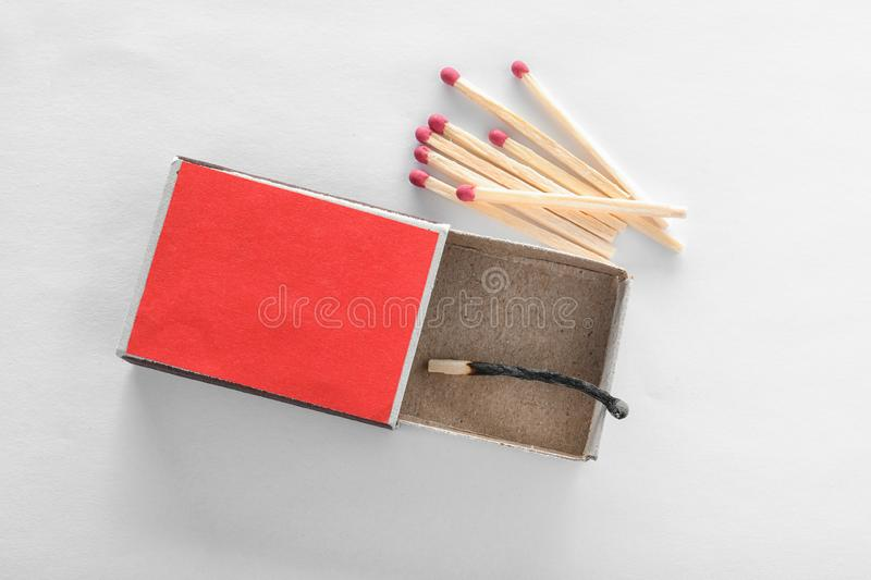 Cardboard box with burnt match and whole ones on white royalty free stock photography