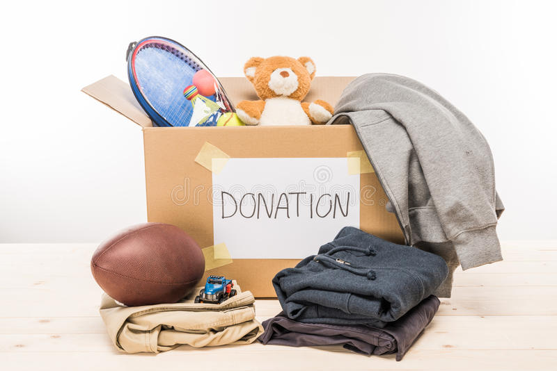 Cardboard box with donation clothes and different objects on white. Donation concept stock image
