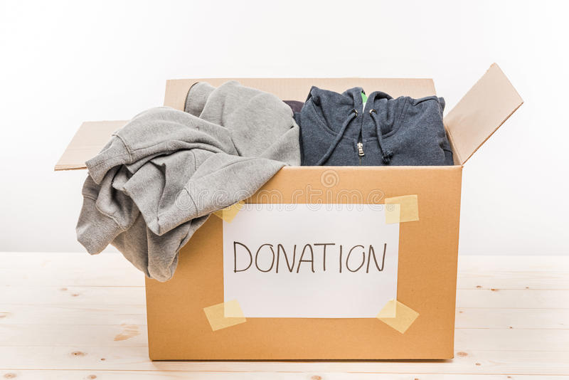 Cardboard box with donation clothes on wooden table on white. Donation concept stock images