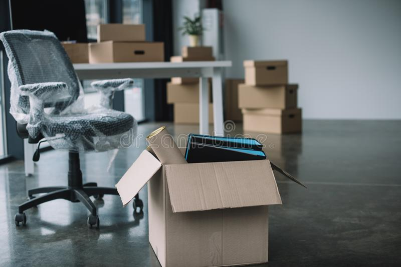 Cardboard box with folders and office supplies in floor. During relocation royalty free stock photography