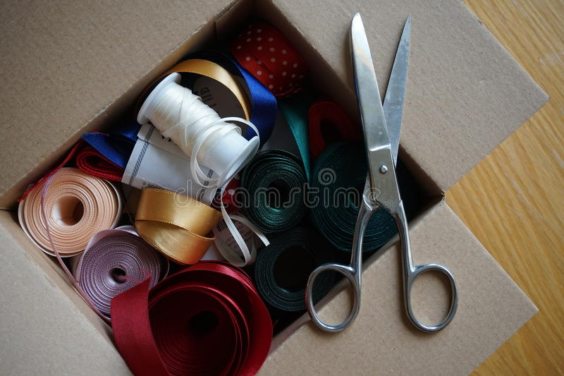 Cardboard box full of equipment for sewing, stitching and for decorating of gifts and presents. For anniversaries stock photo