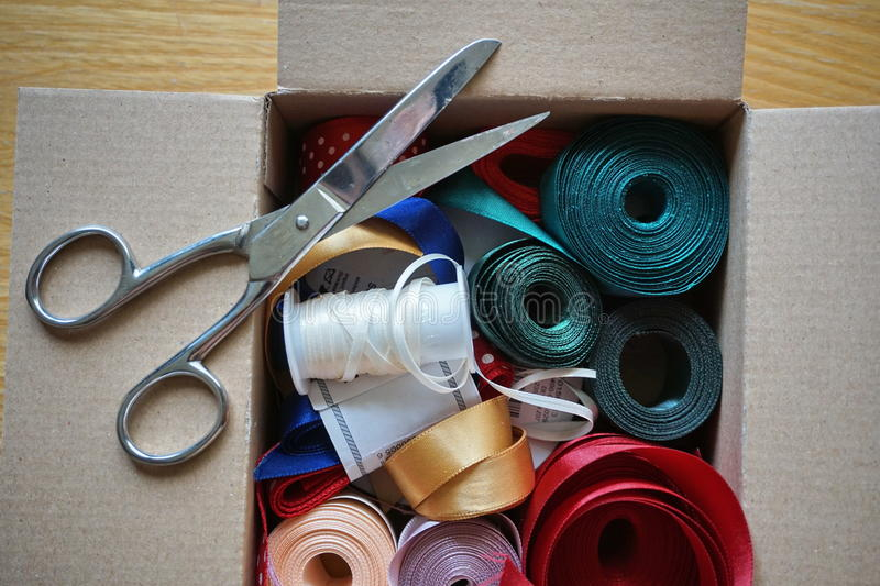 Cardboard box full of equipment for sewing, stitching and for decorating of gifts and presents. For anniversaries stock photos