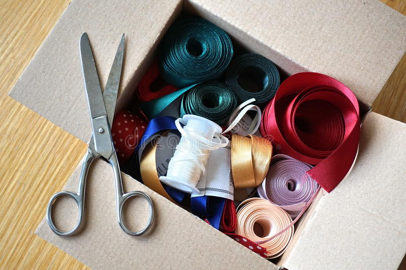 Cardboard box full of equipment for sewing, stitching and for decorating of gifts and presents. For anniversaries royalty free stock images