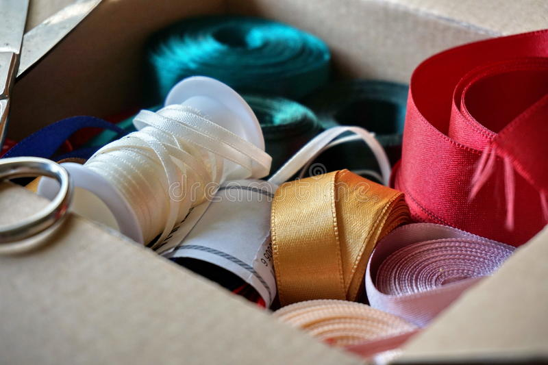 Cardboard box full of equipment for sewing, stitching and for decorating of gifts and presents. For anniversaries royalty free stock photography