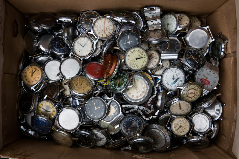 cardboard box with a large pile of old watches. royalty free stock images