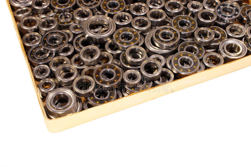 Cardboard box with many small ball bearings isolated on white ba. Ckground stock photo