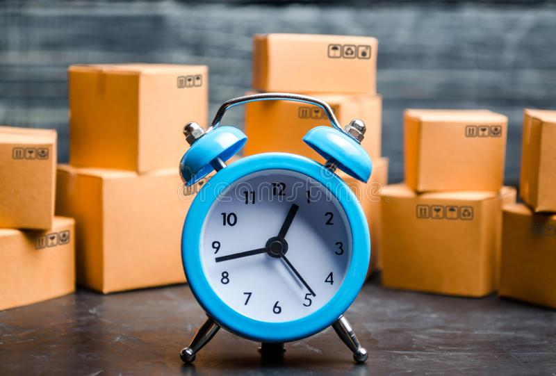 Cardboard boxes and a blue alarm clock. Time of delivery. Limited supply, shortage of goods in stock, hype and consumer fever. royalty free stock photography