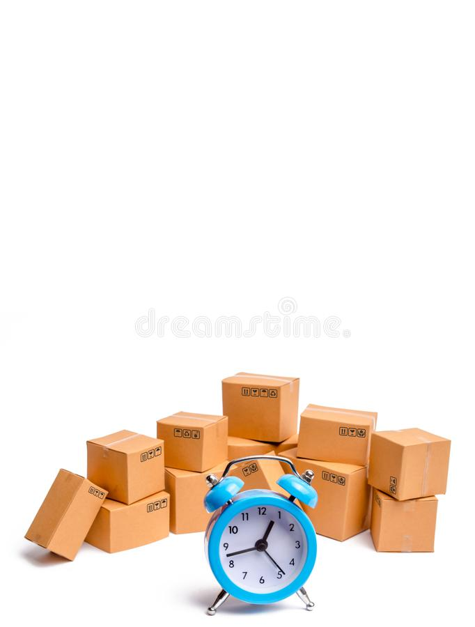 Cardboard boxes and clock on white background. Limited supply, shortage of goods in stock, hype and consumer fever. Time of delivery. concept of buying and royalty free stock photo