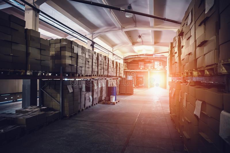 Cardboard boxes with goods on shelves of warehouse in sunlight. Industry distribution, shipping and logistics concept. Toned stock photography