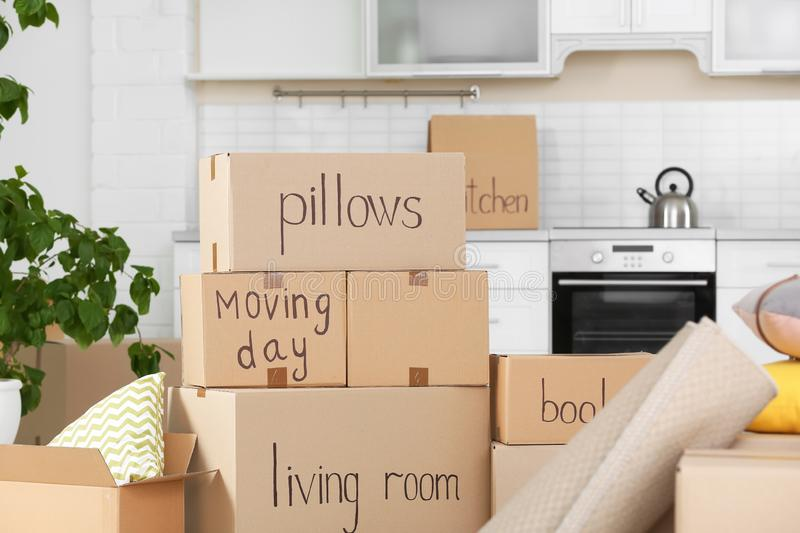 Cardboard boxes and household stuff in kitchen stock image
