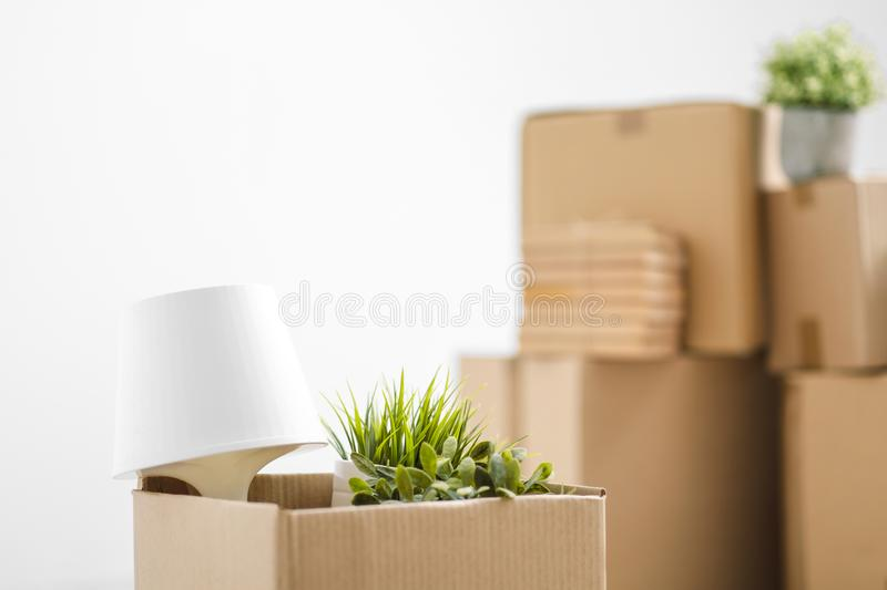 Cardboard boxes with things are stacked on the floor against the background of a white wall close up. Books and table royalty free stock photo