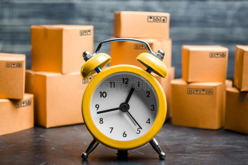 Cardboard boxes and yellow clock. Time of delivery. Limited supply, shortage of goods in stock, hype and consumer fever. Time royalty free stock image