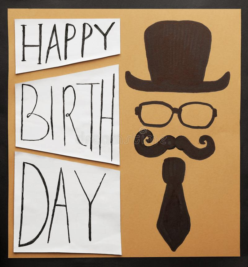 Cardboard card with words HAPPY BIRTHDAY and funny picture on black background. Top view stock images