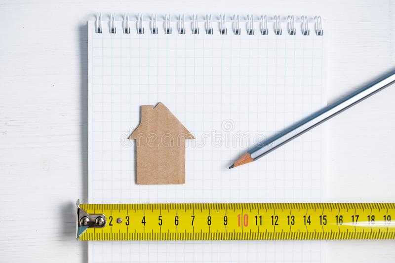 Cardboard cutout house, roulette and pencil on blank sheet of spiral notebook stock images