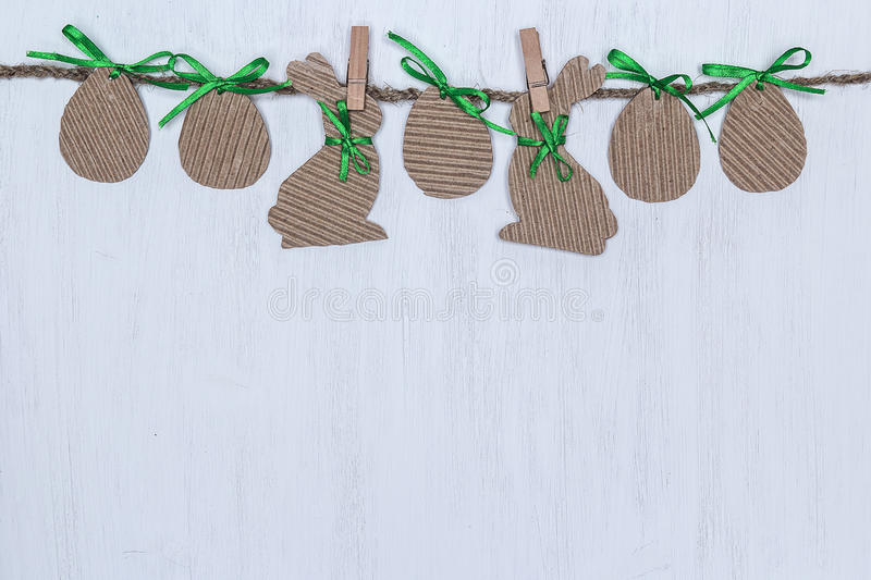 Cardboard Easter eggs and bunnies hanging on white background. Empty space for text stock image