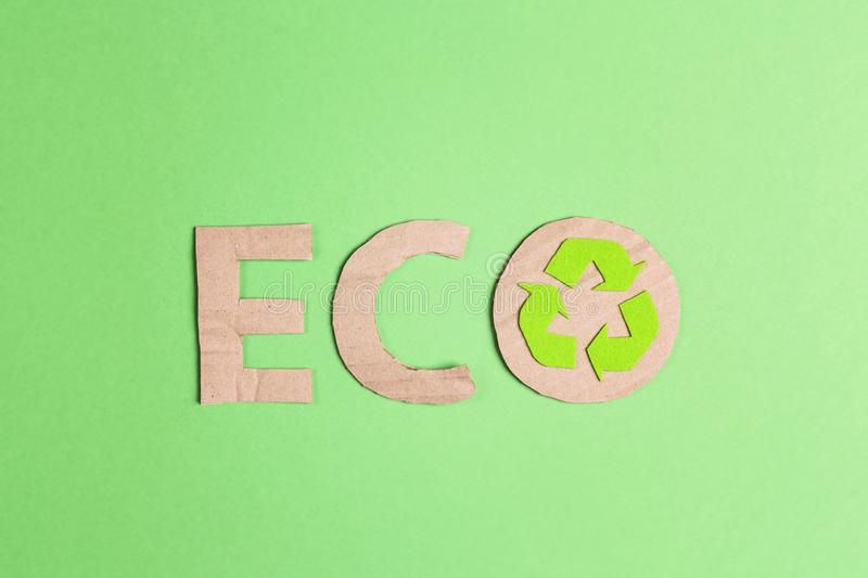 Cardboard eco word with recycle symbol on green background. Recycled cycle sign stock photo