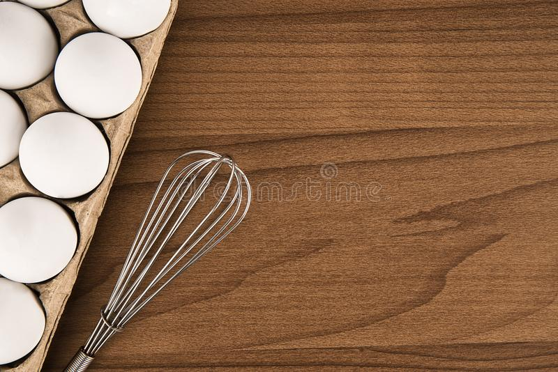 Cardboard egg box and stainless steel whisk on wooden table. Cardboard egg box and stainless steel whisk on wooden table, top view. Cooking concept stock image