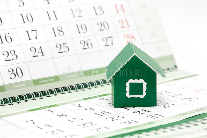 Cardboard green house on the background of the calendar. / Russian translation: Monday, Tuesday, Wednesday, Thursday stock image