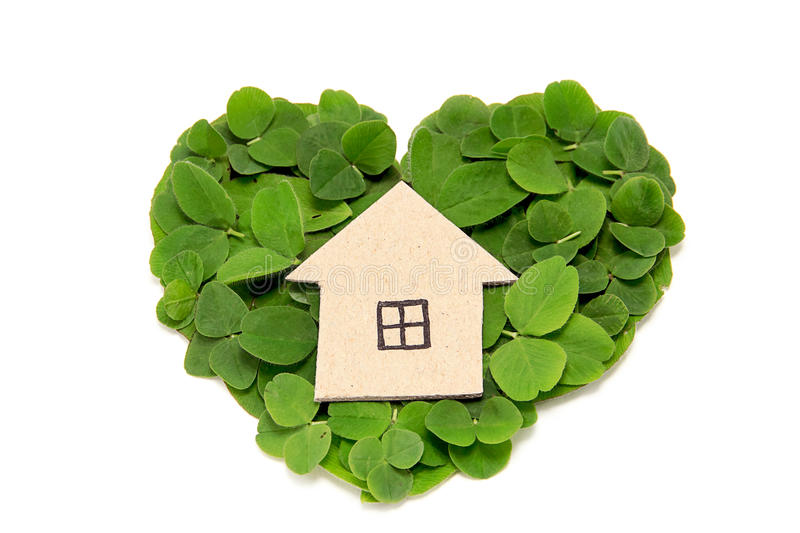 Cardboard house on the heart of a clover leaf. Eco-friendly housing stock image