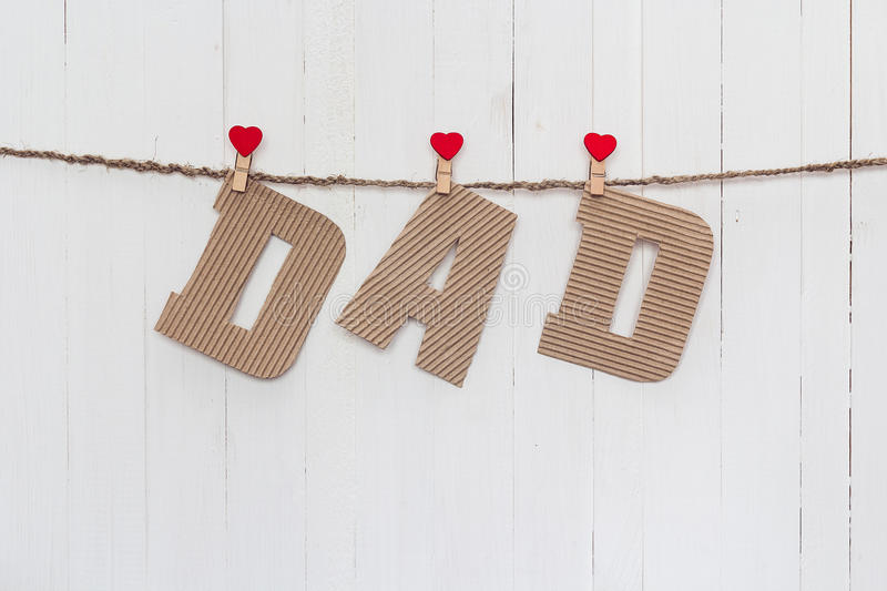 Cardboard letters DAD hanging on clothespins on a white wooden b. Ackground. Happy fathers day concept stock image