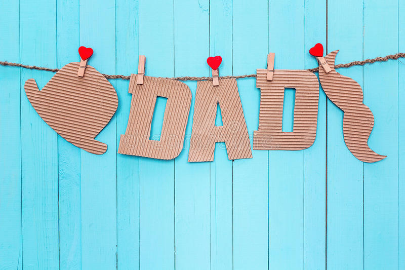 Cardboard letters DAD, hat and mustache hanging on clothespins o. N a blue background. Happy fathers day concept royalty free stock photos