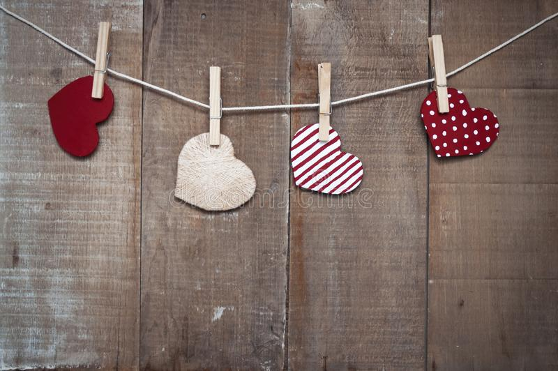 Cardboard Love hearts hanging on the rope with clothespin. Love hearts hanging on rope on grunge background valentine's day stock photo