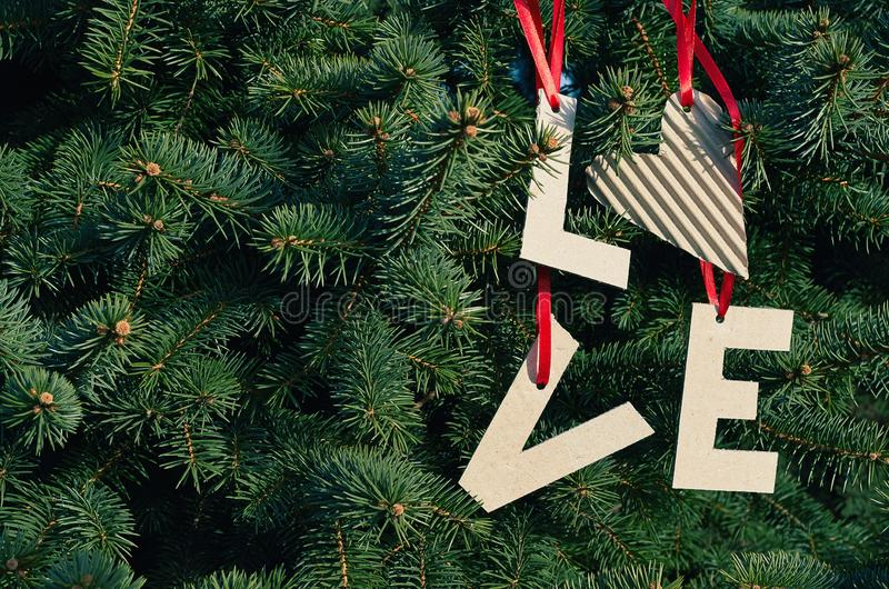 Cardboard LOVE letters hanging on red stripes on green pine tree branches. Holiday postcard template. Space for text, copy,. Lettering royalty free stock images