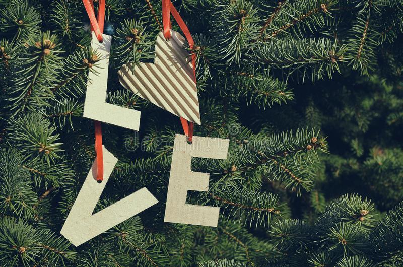 Cardboard LOVE letters hanging on red stripes on green pine tree branches. Holiday postcard template. Space for text, copy,. Lettering stock photo