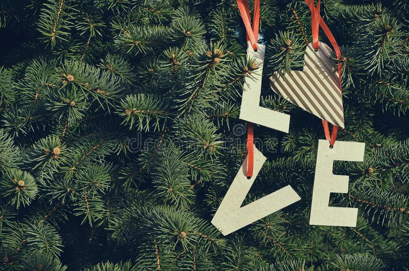 Cardboard LOVE letters hanging on red stripes on green pine tree branches. Holiday postcard template. Space for text, copy,. Lettering stock photos