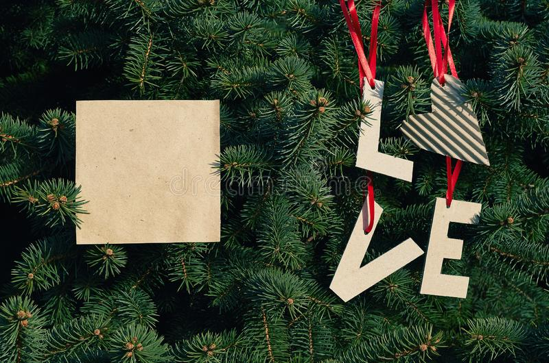 Cardboard LOVE letters hanging on red stripes on green pine tree branches. Holiday postcard template. Space for text, copy,. Lettering royalty free stock photography