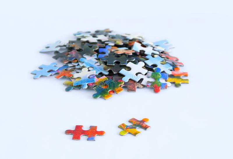 Cardboard multicolored puzzles on white background. Close-up stock photos