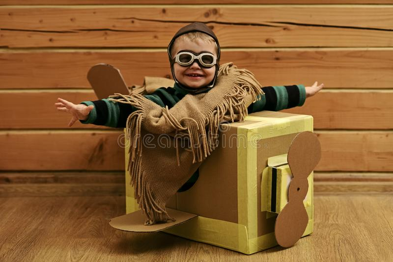 Cardboard plane, childhood, little boy pilot. Cardboard plane, childhood little boy pilot. playing stock photography