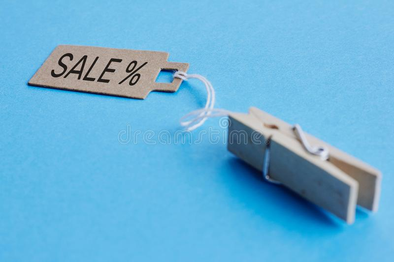 Cardboard price tag with sign sale hanging on wooden clothes clips on blue background. Brown cardboard price tag with sign sale hanging on wooden clothes clips royalty free stock image