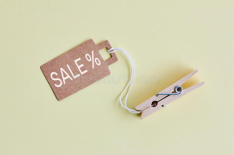 Cardboard price tag with sign sale hanging on wooden clothes clips on pastel yellow background. Brown cardboard price tag with sign sale hanging on wooden royalty free stock photos