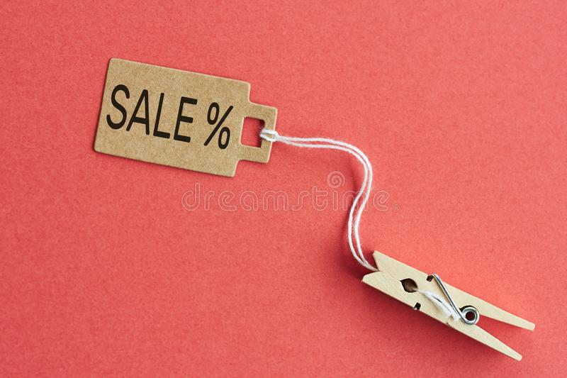 Cardboard price tag with sign sale hanging on wooden clothes clips on red background royalty free stock image