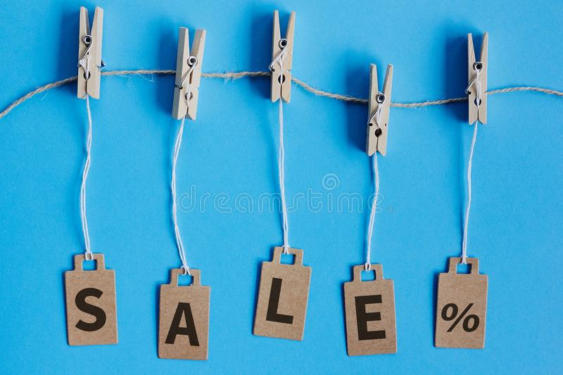 Cardboard price tags with sign sale hanging on wooden clothes clips on blue background. Brown cardboard price tags with sign sale hanging on wooden clothes clips royalty free stock photos