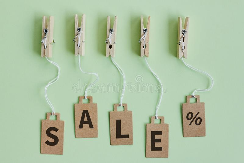 Cardboard price tags with sign sale hanging on wooden clothes clips on pastel green background. Brown cardboard price tags with sign sale hanging on wooden stock photography