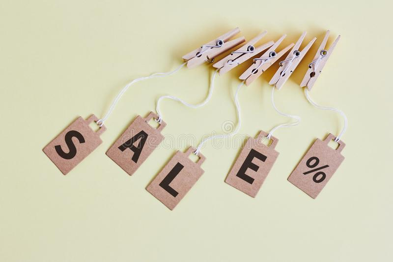 Cardboard price tags with sign sale hanging on wooden clothes clips on pastel yellow background. Brown cardboard price tags with sign sale hanging on wooden royalty free stock photo