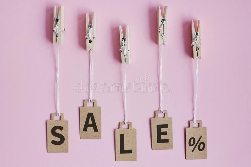 Cardboard price tags with sign sale hanging on wooden clothes clips on pink background. Brown cardboard price tags with sign sale hanging on wooden clothes clips stock images