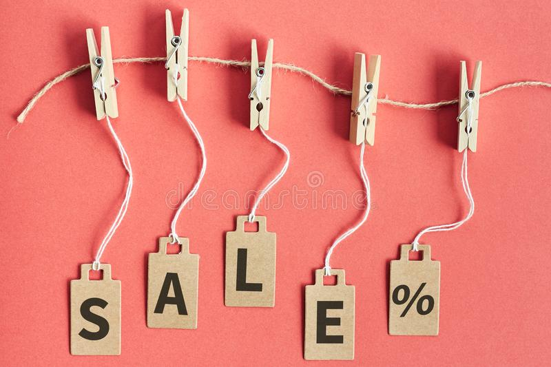 Cardboard price tags with sign sale hanging on wooden clothes clips on red background. Brown cardboard price tags with sign sale hanging on wooden clothes clips stock images