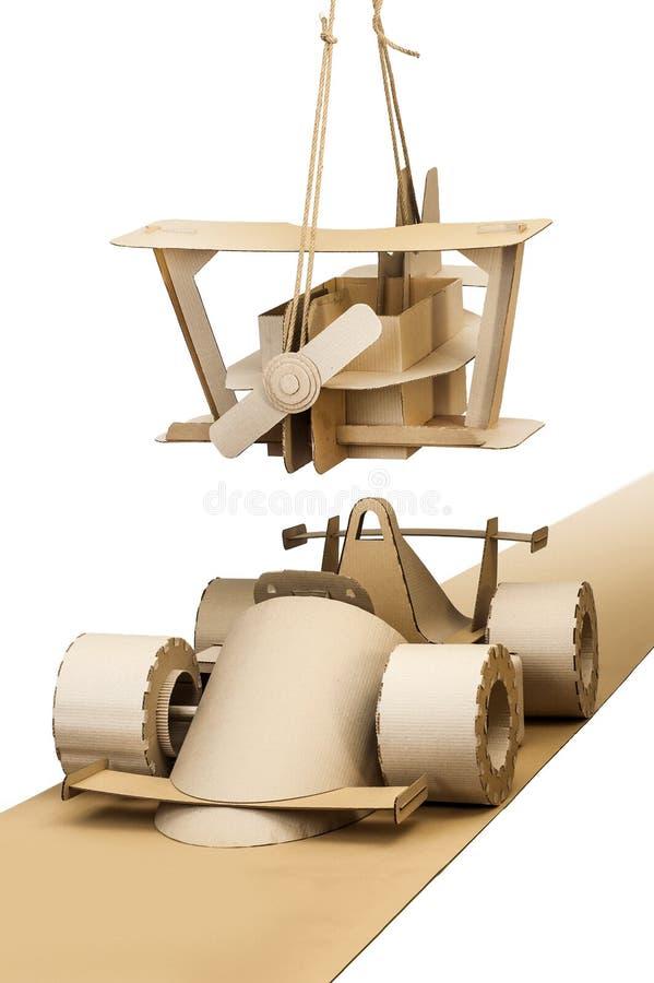 Cardboard racing car and cardboard plane. Photo of cardboard racing car and plane on white background royalty free stock photos
