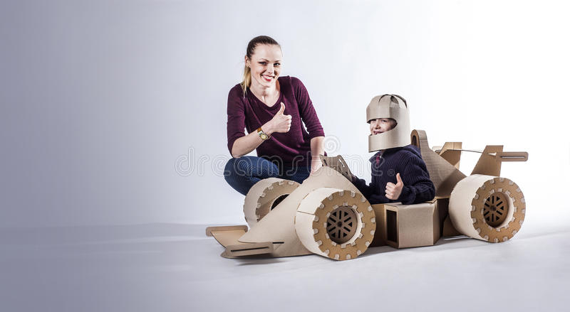 Cardboard racing car and happy family. thumbs up. Mother and son playing with a large cardboard racing car. thumbs up. happy family royalty free stock photography
