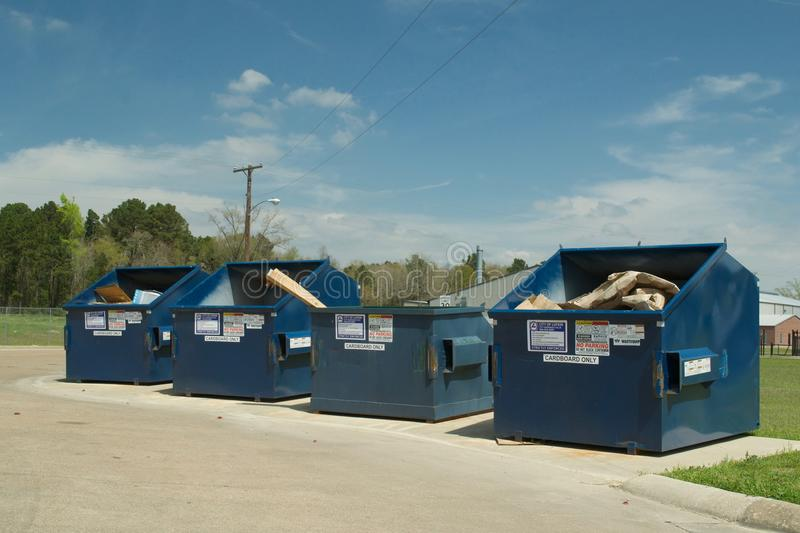 Cardboard Recycling Dumpster Bins. Metal, blue recycling dumpster bins for recycling cardboard on sunny day with blue sky and clouds stock images