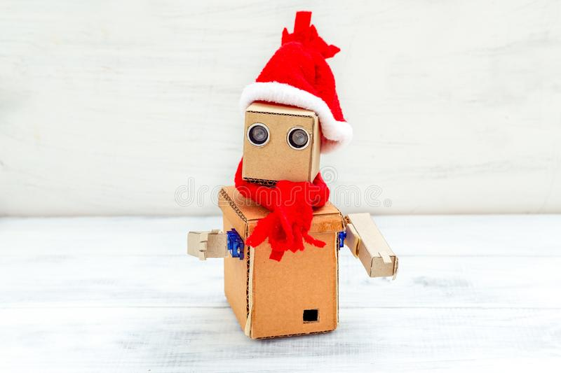 Cardboard robot with hands in santa hat on a white wooden background. Christmas composition royalty free stock image