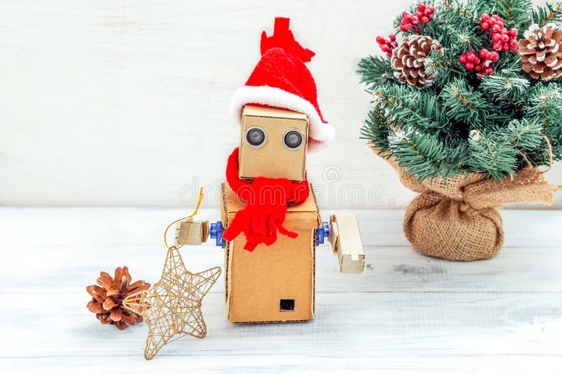 Cardboard robot with hands in santa hat on a white wooden background and christmas tree. Christmas composition royalty free stock photo