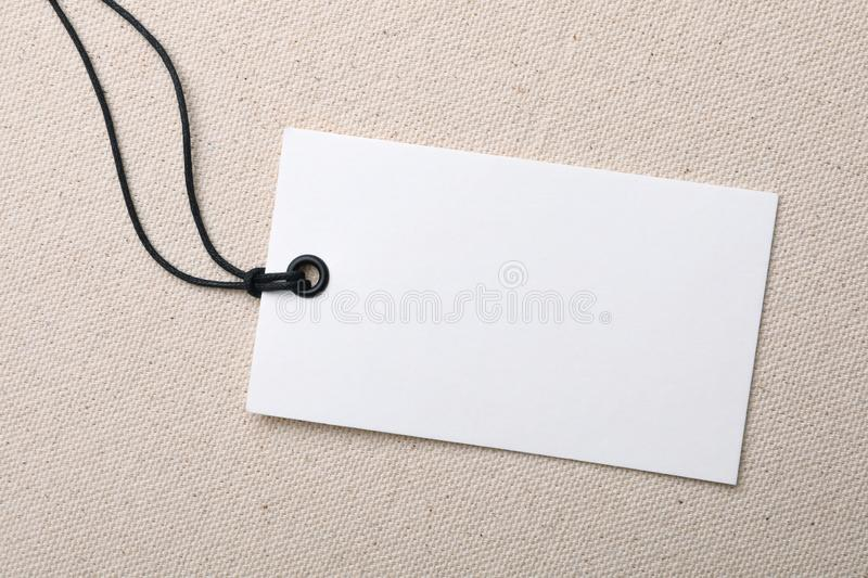 Cardboard tag with space for text on color fabric. Top view royalty free stock photo